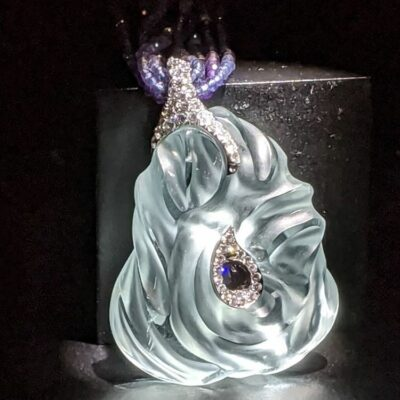 Hand-carved aquamarine pendant on display at Wilensky